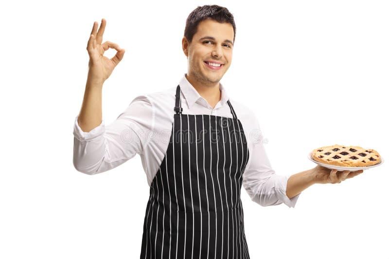 Lächelnder junger Mann mit einem Schutzblech, das eine Torte und die Herstellung eines symbolisierenden Zeichens hält lizenzfreie stockbilder