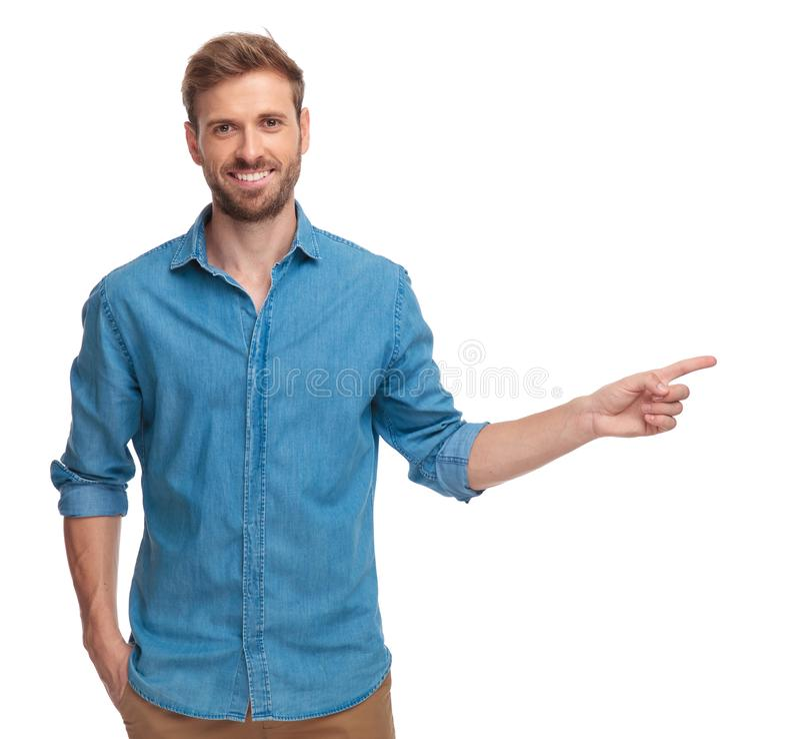 Lächelnder junger Mann zeigt auf Seite stockfotos