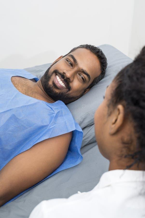 Lächelnder junger Patient, der Radiologe-During-Röntgenstrahl-Scan betrachtet lizenzfreie stockfotos