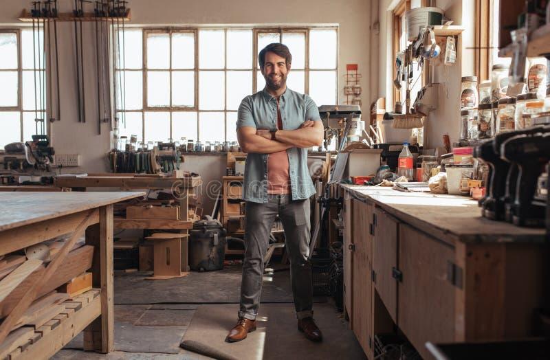 Lächelnder junger Tischler, der voll in seiner Werkstatt von Werkzeugen steht stockfotografie