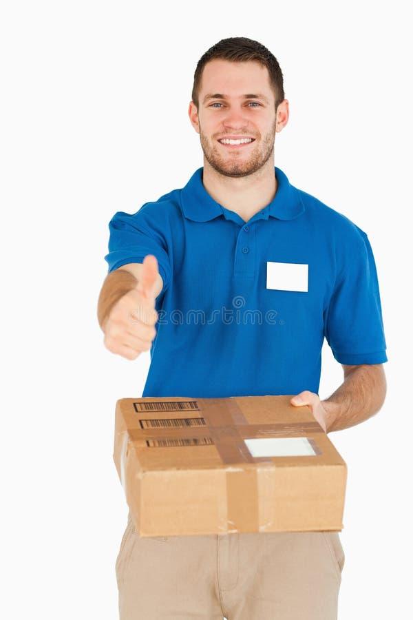 Lächelnder junger Verkäufer mit dem Paket, das Daumen aufgibt stockbild