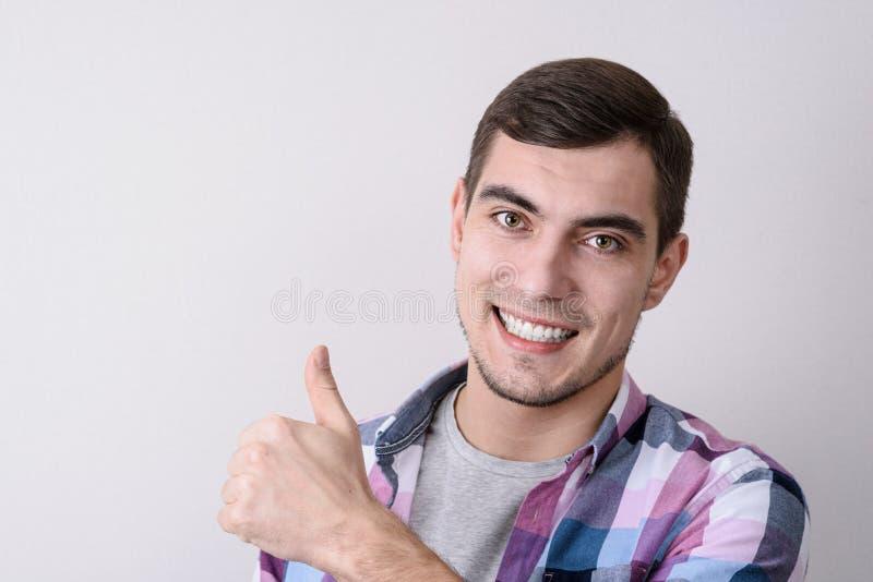 Lächelnder kaukasischer Mann, der Kamera betrachtet und Daumen oben über grauem Hintergrund zeigt lizenzfreie stockbilder