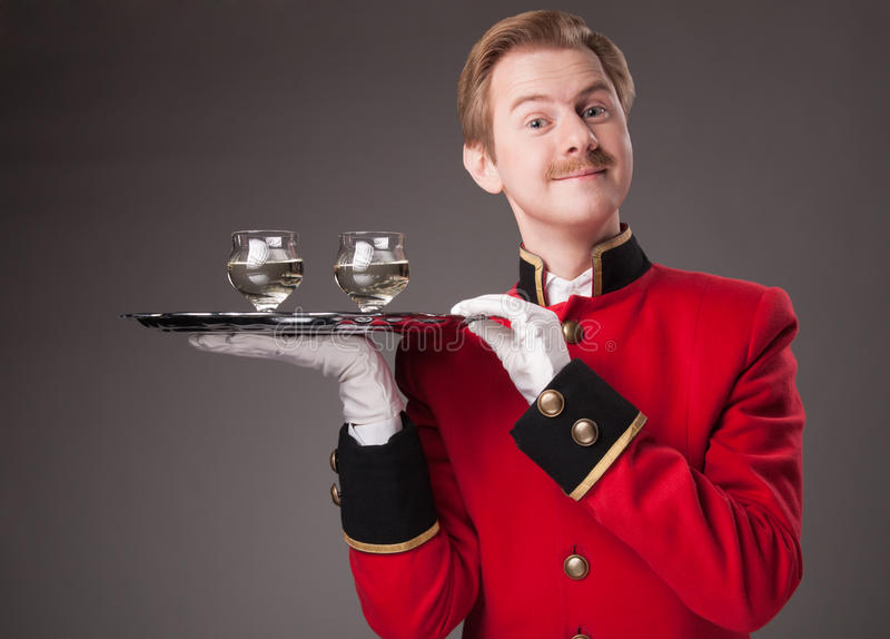 Lächelnder Kellner in der roten Uniform stockbilder