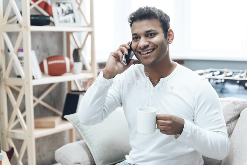 Lächelnder Kerl in der Freizeitbekleidung unter Verwendung des Handys lizenzfreie stockfotografie