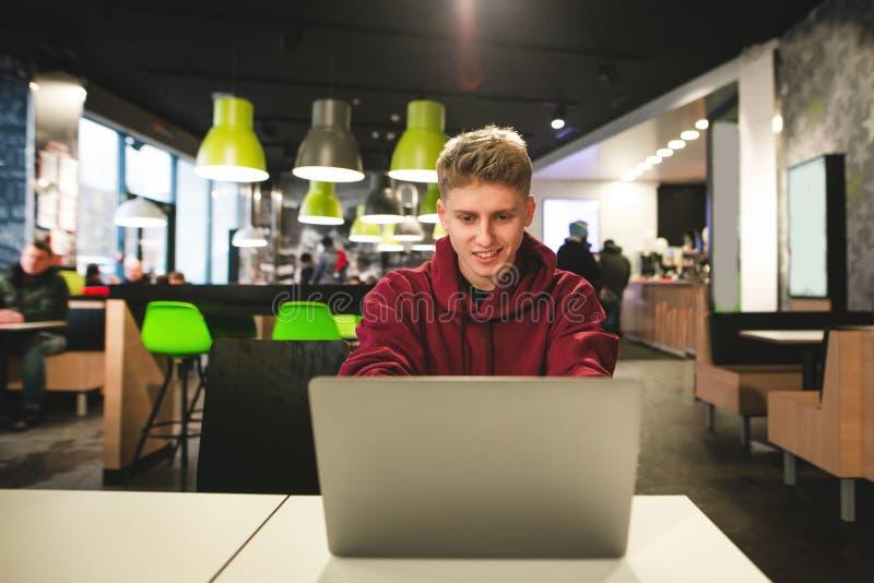 Lächelnder Kerl sitzt in einem Schnellimbisscafé, betrachtet den Laptopschirm und -lächeln lizenzfreie stockfotos