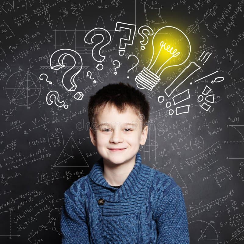 Lächelnder Kinderschuljunge mit Glühlampe auf Hintergrund mit Formeln lizenzfreies stockfoto