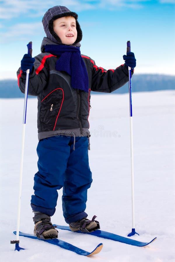 Lächelnder Kindjungen-Skifahrer, der im Schnee steht stockbild