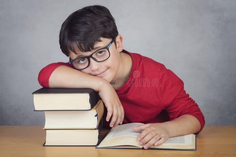 Lächelnder kleiner Junge, der auf Büchern sich lehnt stockfotos