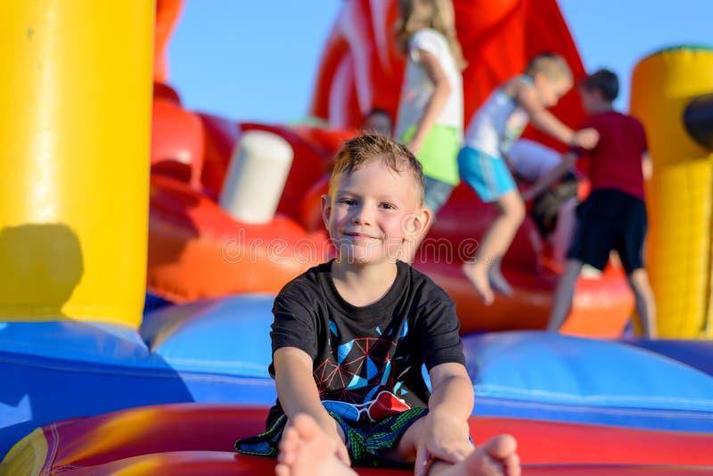 Lächelnder kleiner Junge, der auf einem springenden Schloss sitzt lizenzfreie stockfotos
