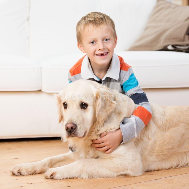 Lächelnder kleiner Junge, der mit einem golden retriever spielt stockfoto