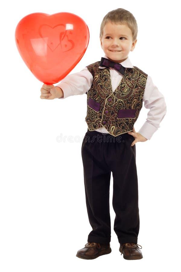 Lächelnder kleiner Junge gibt einen roten Ballon stockfotografie