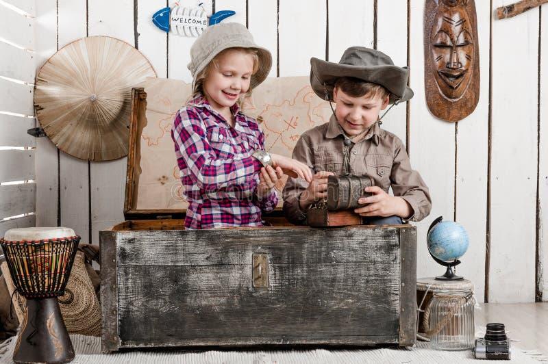 Lächelnder kleiner Junge und Mädchen entdeckt Schatz stockfoto