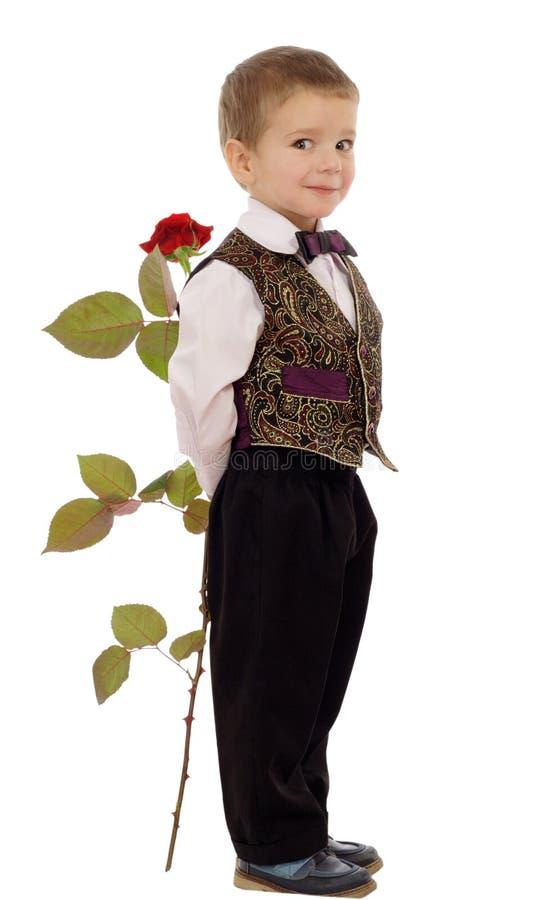 Lächelnder kleiner Junge versteckt eine Rose stockfotografie