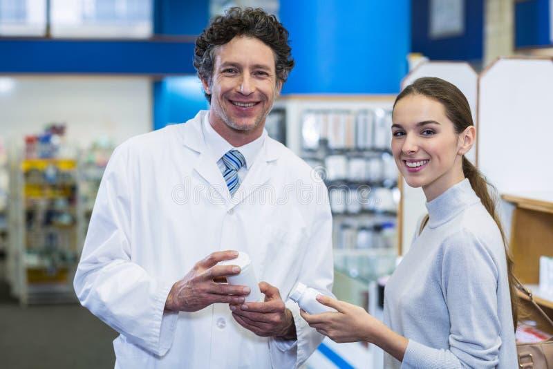 Lächelnder Kunde und Apotheker, die Drogenflasche im Krankenhaus halten lizenzfreie stockfotos