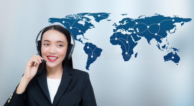 Lächelnder Kundendienst der schönen asiatischen Frau, der auf Kopfhörer mit Weltkartekommunikation spricht stockbild