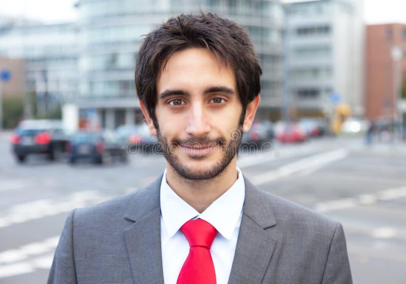 Lächelnder lateinischer Geschäftsmann mit Bart in der Stadt lizenzfreie stockfotos