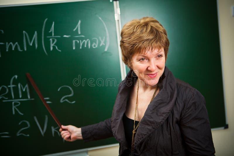 Lächelnder Lehrer mit Nadelanzeige stockfoto