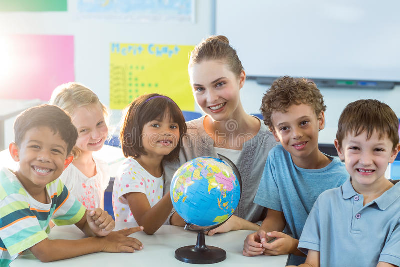 Lächelnder Lehrer und Schulkinder mit Kugel auf Tabelle lizenzfreie stockfotografie