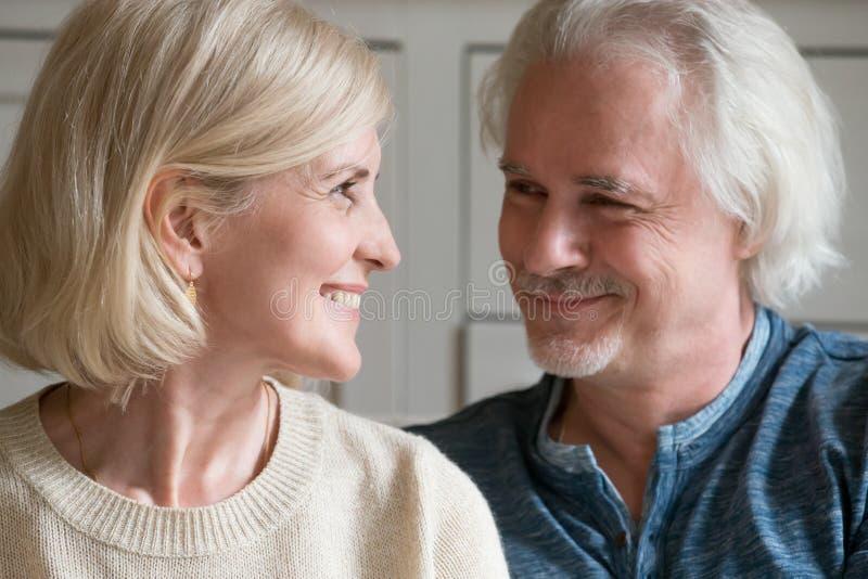 Lächelnder liebevoller reifer Mann und Frau, die einander betrachten stockbilder