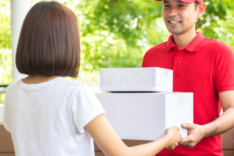 Lächelnder Lieferer, der Pakete an eine Frau liefert stockbild