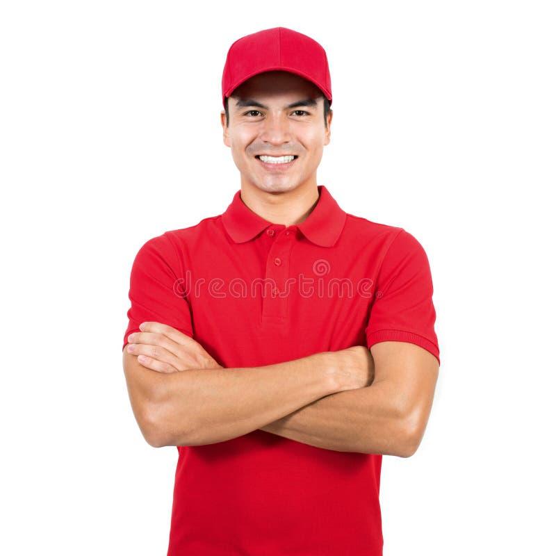 Lächelnder Lieferer in der roten Uniform, die mit dem Arm gekreuzt steht stockbild