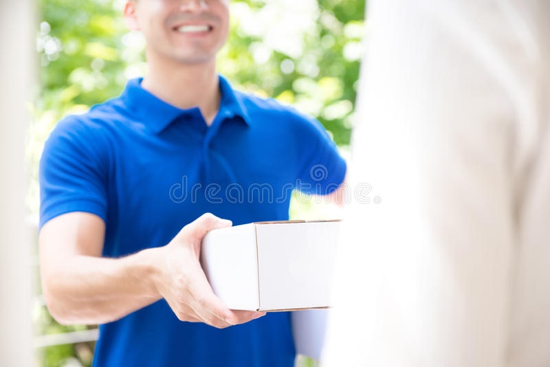 Lächelnder Lieferer im blauen einheitlichen liefernden Paketkasten zur Empfänger lizenzfreies stockbild