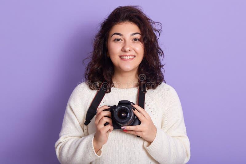 Lächelnder lustiger Fotograf, der im Studio über lila Hintergründe steht, direkt auf die Kamera schaut, Foto hält stockbild