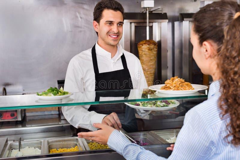 Lächelnder männlicher Arbeitskraftumhüllungskunde mit Lächeln an shawarma plac stockfotos