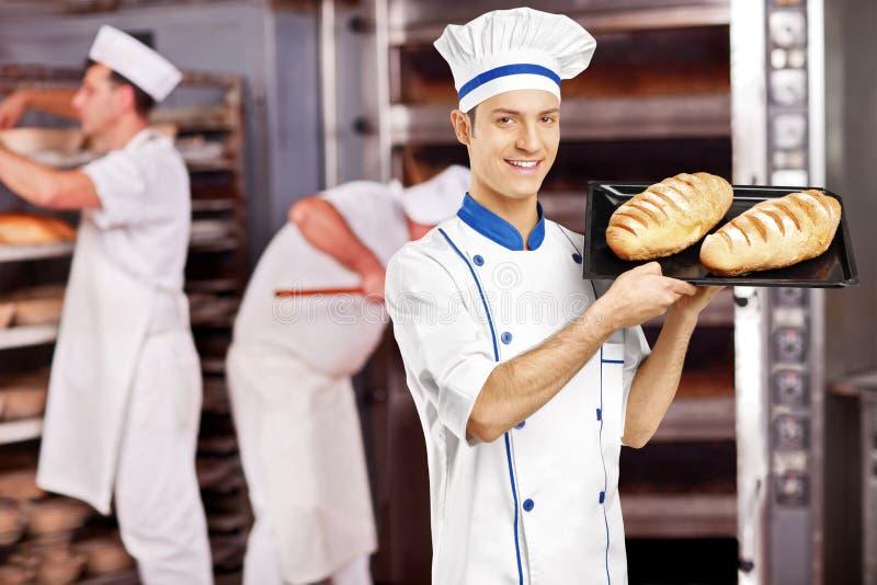 Lächelnder männlicher Bäcker, der mit frisch gebackenen Broten in der Bäckerei aufwirft stockbild