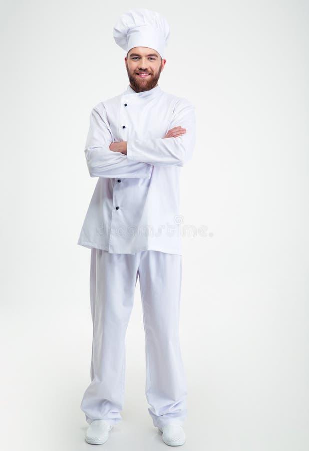 Lächelnder männlicher Chefkoch, der mit den Armen gefaltet steht stockbilder