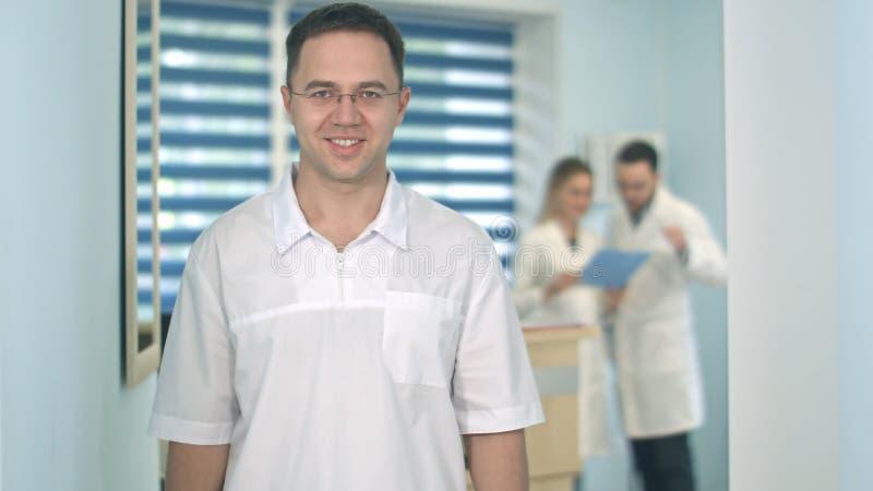 Lächelnder männlicher Doktor in den Gläsern, die Kamera während medizinisches Personal arbeitet an dem Hintergrund betrachten stockfotografie