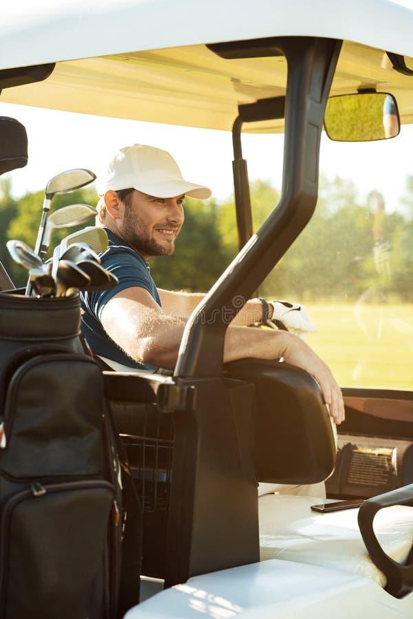 Lächelnder männlicher Golfspieler, der in einem Golfmobil sitzt lizenzfreie stockfotografie