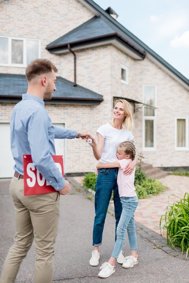 lächelnder männlicher Grundstücksmakler mit dem Verkaufszeichen, das der jungen Frau Schlüssel gibt lizenzfreie stockfotos
