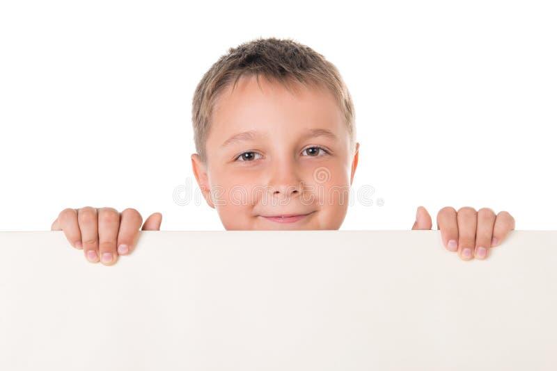 Lächelnder männlicher Jugendlicher des hübschen Jungen, der hinter weißer Platte auf weißem Hintergrund aufwirft Reklamefläche fü stockbild