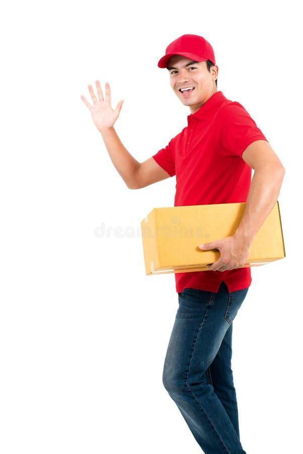 Lächelnder machender Lieferer hallo oder abgelegene Geste beim Halten des Kastens stockbilder