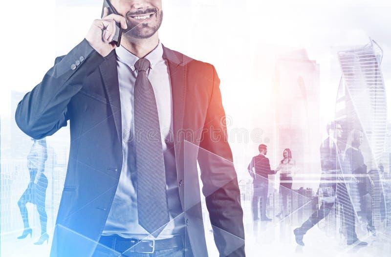 Lächelnder Mann auf Telefon und Team in Moskau-Stadt stockbild