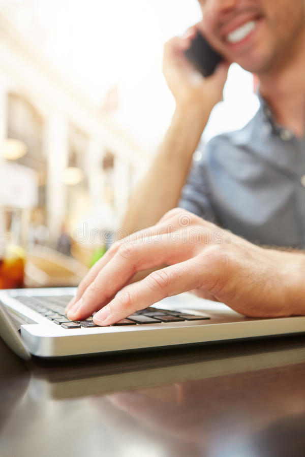 Lächelnder Mann beim Telefonanruf, der an Laptop arbeitet lizenzfreie stockbilder