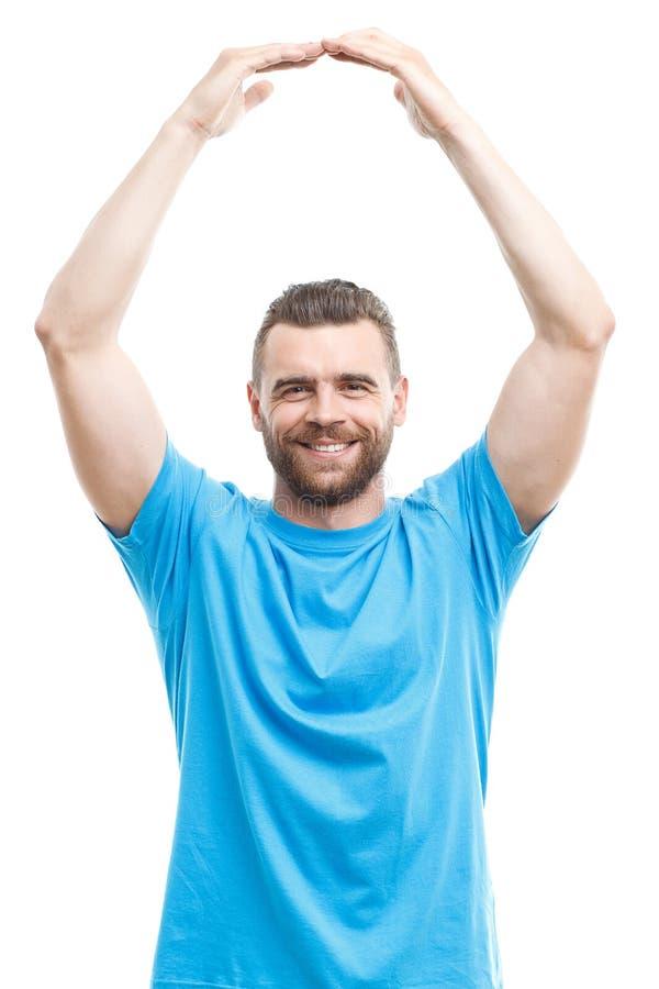 Lächelnder Mann, der Arme über seinem Kopf hält stockbild