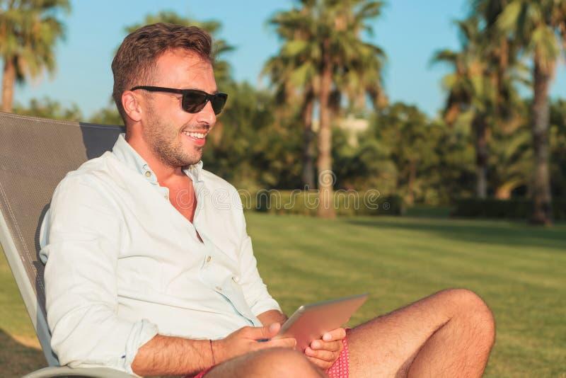 Lächelnder Mann, der auf dem langen Stuhl hält eine Tablette sitzt lizenzfreie stockbilder
