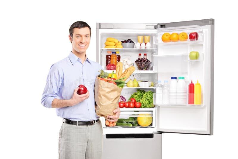 Lächelnder Mann, der eine Tasche vor Kühlschrank hält stockfoto