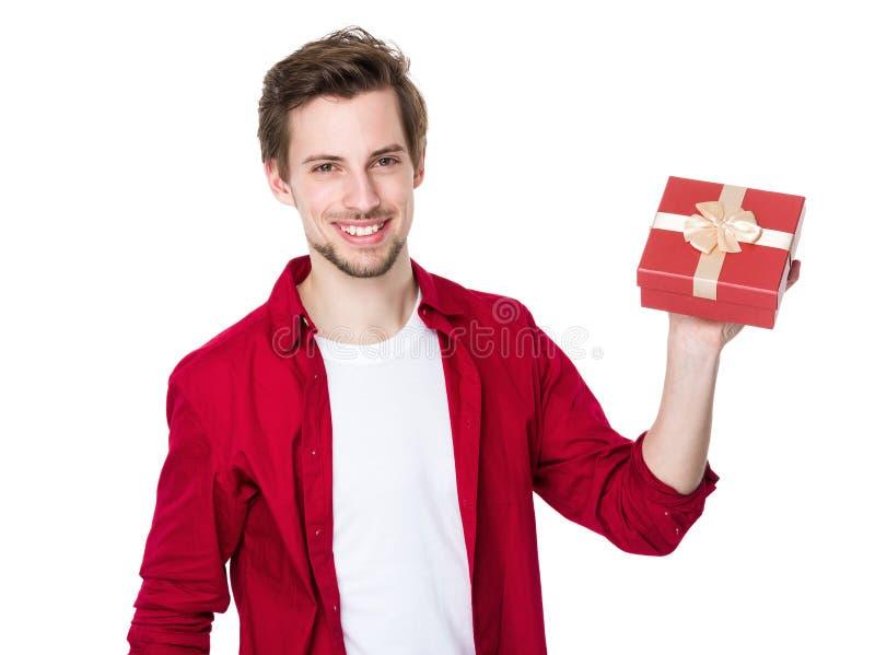 Lächelnder Mann, der Geschenk hält stockfotografie