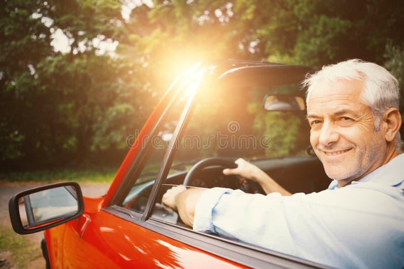 Lächelnder Mann, der rotes Auto fährt stockbilder