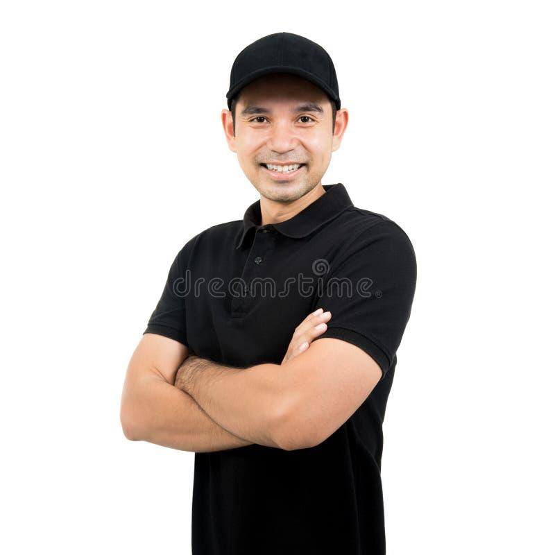 Lächelnder Mann in der schwarzen Uniform, die mit dem Arm gekreuzt steht stockfotos