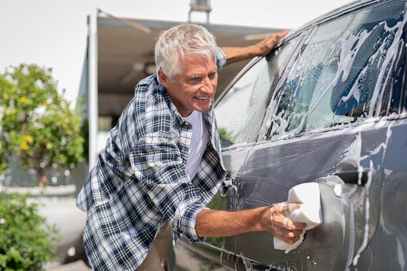 Lächelnder Mann, der sein Auto wäscht stockfotografie