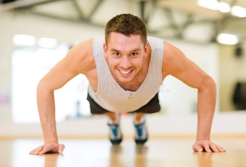 Lächelnder Mann, der StoßUPS in der Turnhalle tut lizenzfreie stockfotos