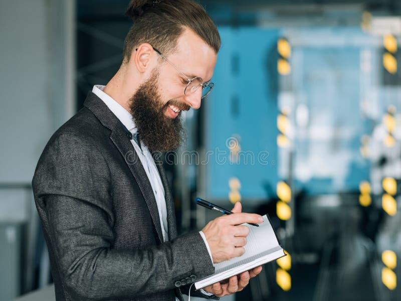Lächelnder Mann, der tägliche Planergeschäftstagesordnung schreibt stockfotografie