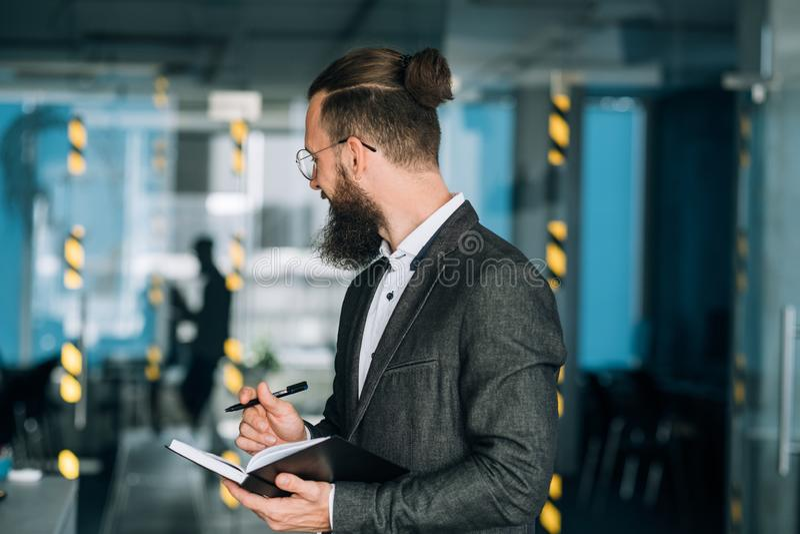 Lächelnder Mann, der tägliche Planergeschäftstagesordnung schreibt lizenzfreies stockbild