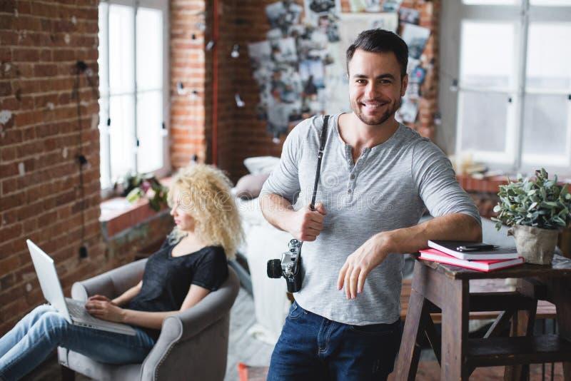 Lächelnder Mann in einer grauen T-Shirt und Jeansstellung und eine Frau, die mit einem Laptop im Dachboden sitzt lizenzfreies stockfoto