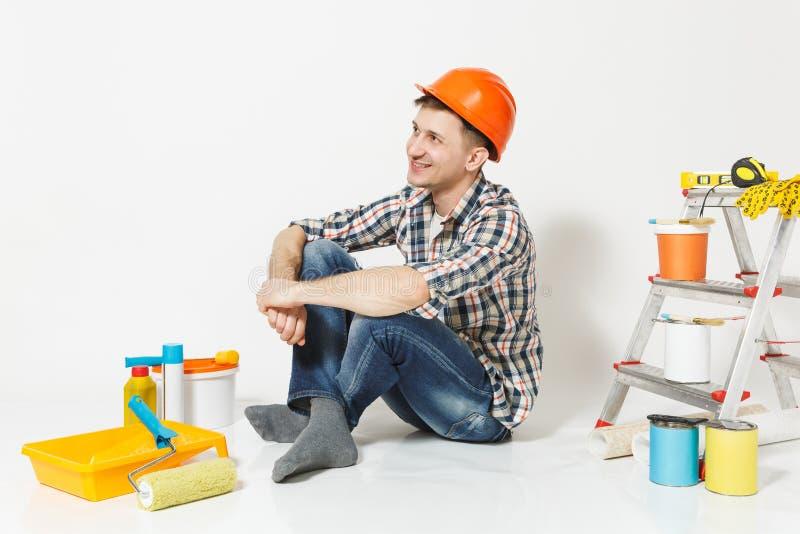 Lächelnder Mann im orange Schutzhelm, der beiseite, sitzend mit Instrumenten nach der Erneuerungswohnung an lokalisiert sucht stockfotos