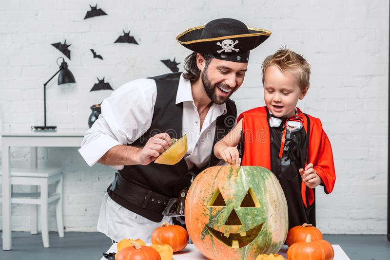 lächelnder Mann im Piratenkostüm und -sohn in Vampirshalloween-Kostüm, das zusammen Kürbis untersucht stockbilder